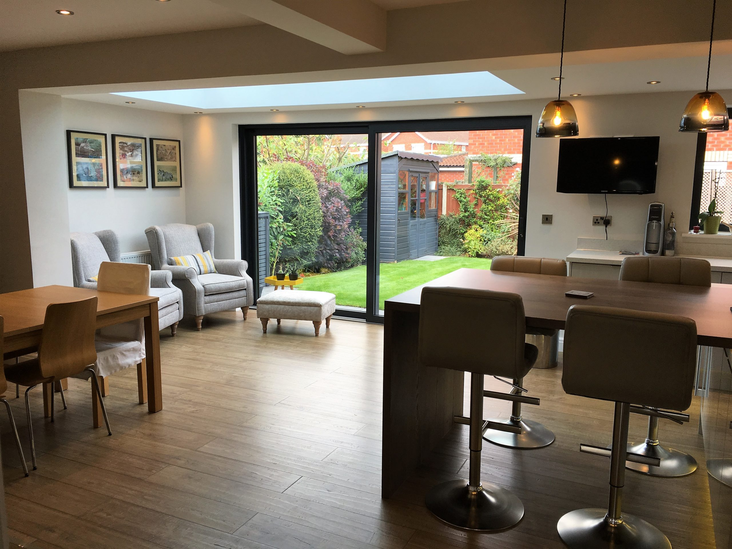 Wide angle view of modern kitchen and living area in a single storey extension