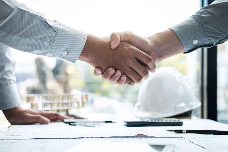 handshake over desk of construction documents